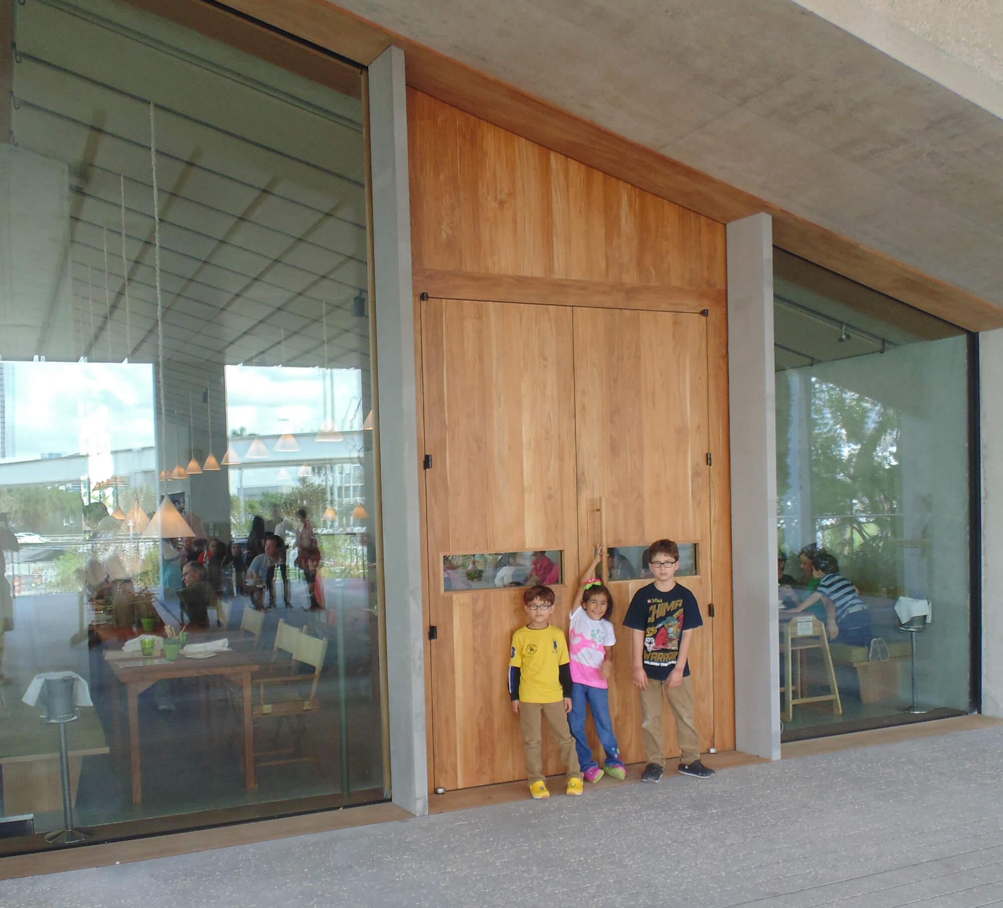 TEAK ENTRANCE DOORS TO RESTAURANT IN THE MIAMI PEREZ ART MUSEUM.